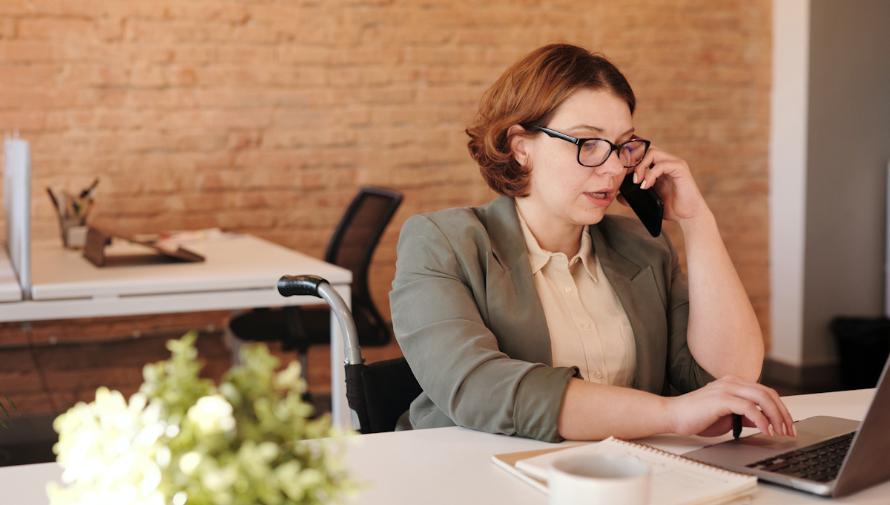 kobieta przy stole rozmawiająca przez telefon, zdjęcie Marcus Aurelius z Pexels